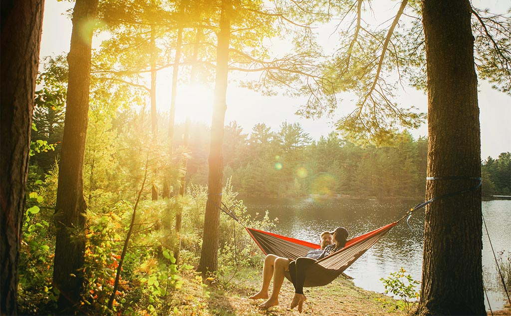 Oklahoma offers many social distancing friendly summer outdoor activities. Here, a young couple relaxes in a hammock next to an Oklahoma lake.