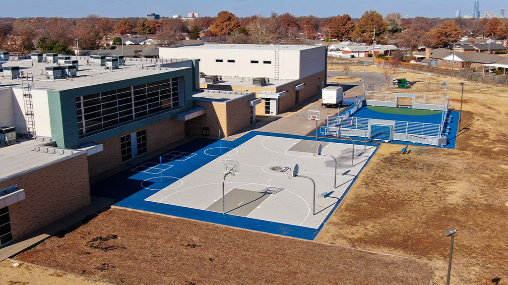 OKCPS Southeast Middle School with finished basketball and futsal courts during the second phase of construction by Fields & Futures