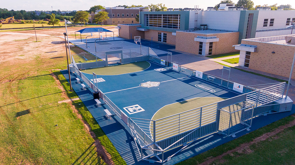OKCPS Southeast Middle School with completed basketball and football courts during field construction by Fields & Futures