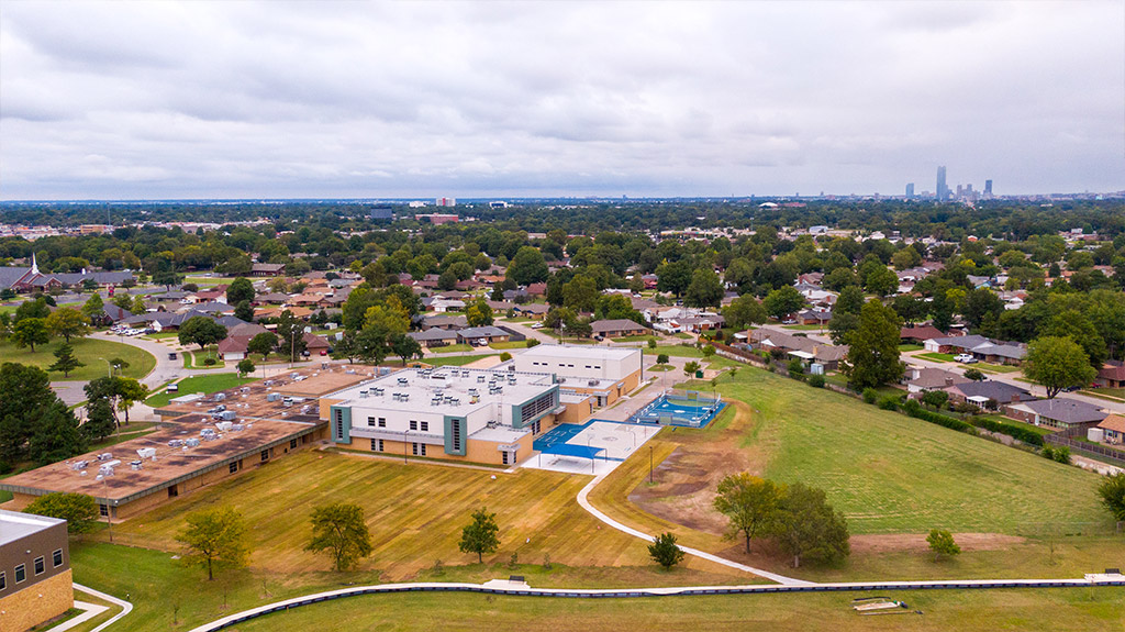 Downtown Oklahoma City in the background of OKCPS Southeast Middle School with new sod on athletic field during field construction by Fields & Futures