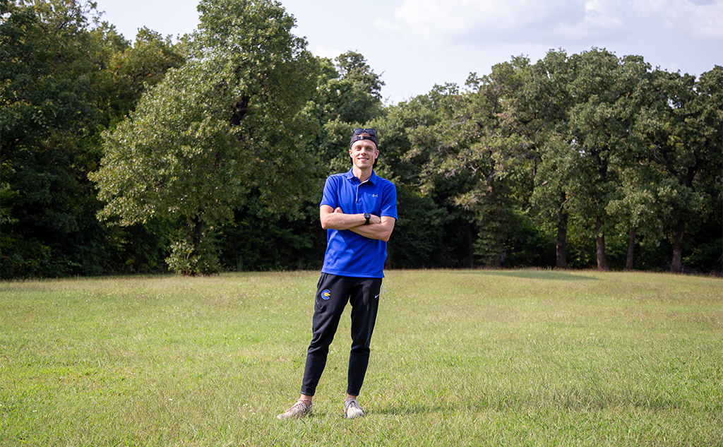Classen SAS at Northeast Cross Country head coach, Carsen Moon, standing on the Comets' practice trail at Lacy Park in Oklahoma City