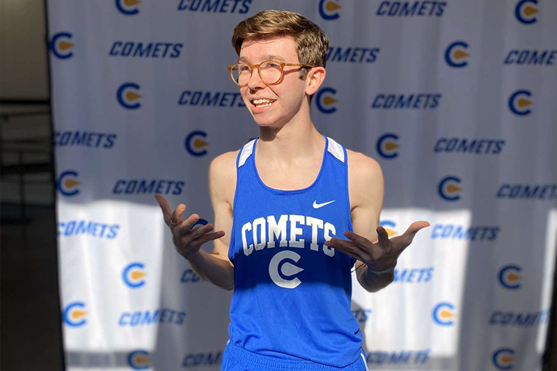 Classen SAS High School at Northeast cross country and track athlete Aiden Kirkpatrick standing against a Classen SAS photo backdrop