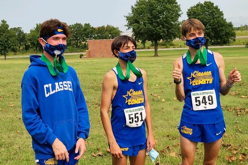 Aiden Kirkpatrick and other Classen SAS High School at Northeast cross country runners posing with their race medals