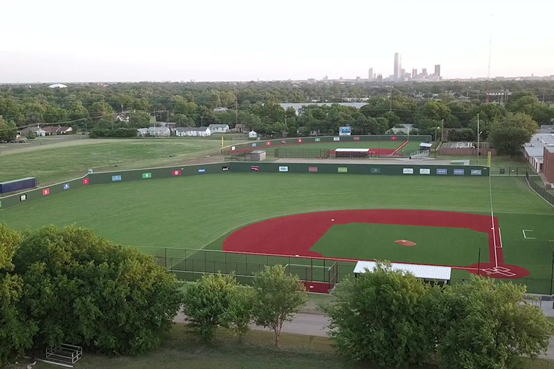 An OKCPS softball field below the OKC skyline in the Fields & Futures Why We Care Campaign Video.