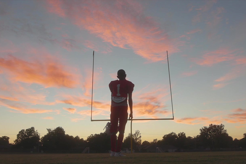 An OKCPS student-athlete standing on a footbal field in Fields & Futures Why We Care Campaign Video