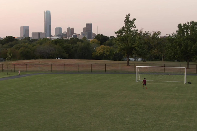 An OKCPS soccer field below the OKC skyline in the Fields & Futures Why We Care Campaign Video.