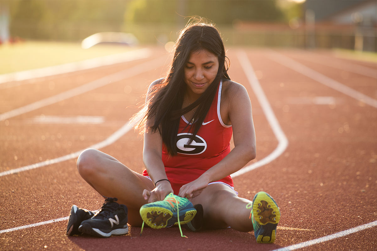 Why-We-Care-Students-Janet-Herrera-sitting-on-the-running-track