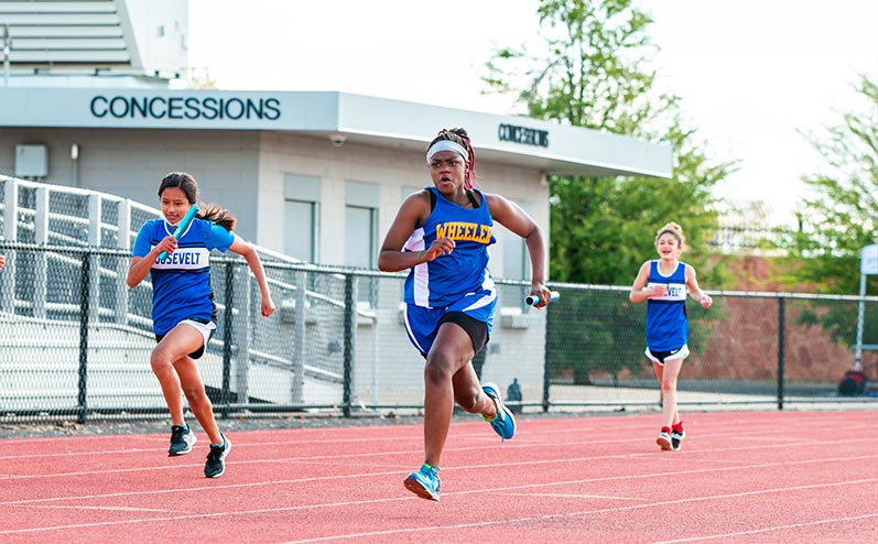 Fields & Futures All-City Track Meet Blog female middle school athletes competing in a relay race