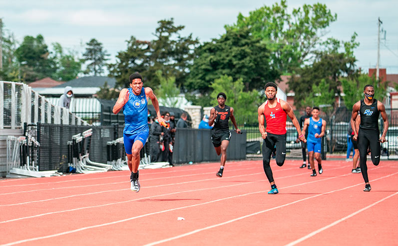 Fields & Futures All-City Track Meet Blog male high school student-athletes running in a relay race