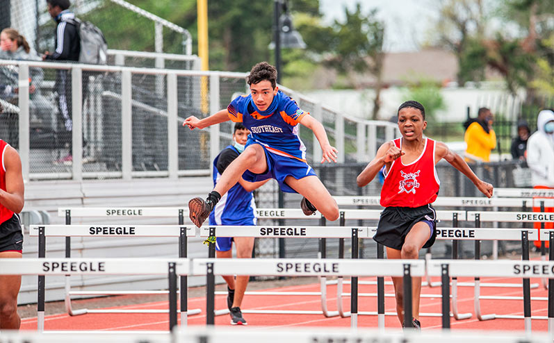 Fields & Futures All-City Track Meet Blog male middle school athletes competing in hurdles