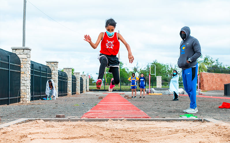 Fields & Futures All-City Track Meet Blog male middle school athlete competing in the long jump