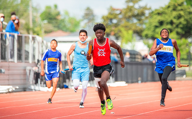 Fields & Futures All-City Track Meet Blog male middle school athletes competing in a relay race