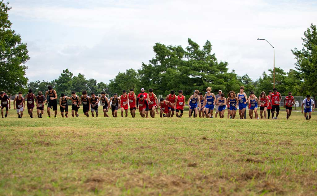 Fields and Futures All-City Athletic Conference blog feature image of OKCPS high school boys lined up at the starting line of the conference championship cross country meet