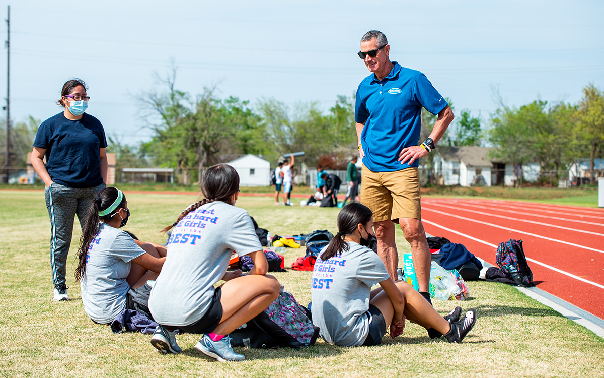 David Crynes talking with track and field student-athletes