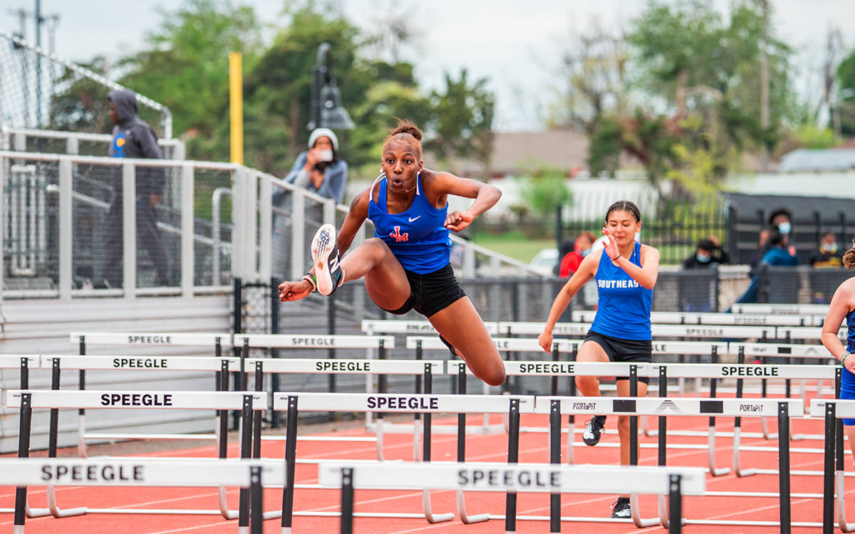 Track and field student-athlete jumping over hurdle at Speegle Stadium