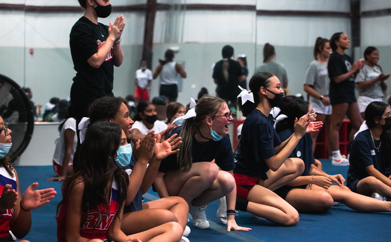 Fields & Futures blog 2021 OKCPS Cheer Clinic Wrap-Up story image of a group of cheerleaders laughing at cheer clinic