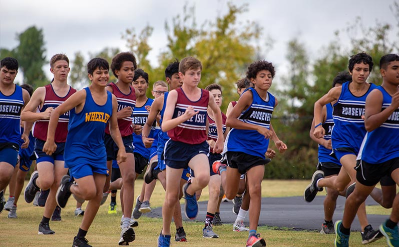 Fields & Futures Simon Greiner Track & Field Program Coach's Interview with John Zehr blog post story image of middle school cross country athletes from Oklahoma City Public Schools running in a cross country race