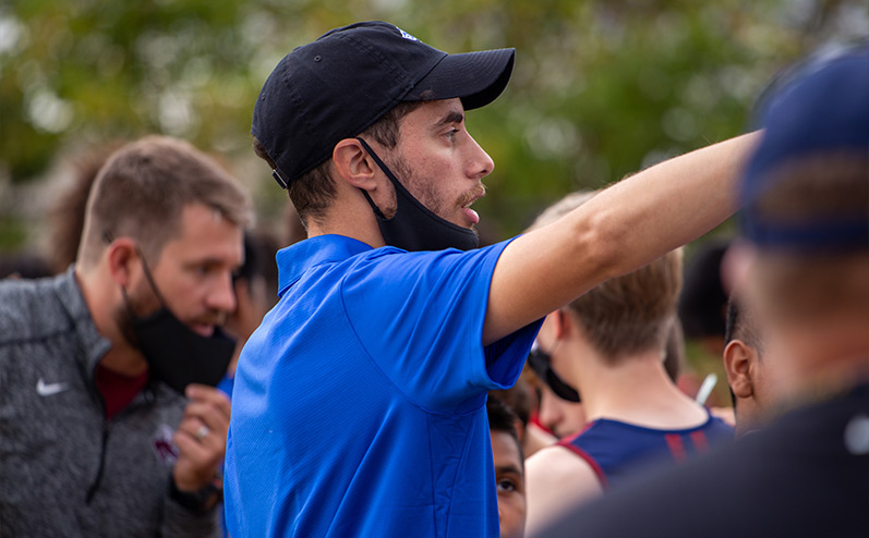 Fields & Futures Simon Greiner Track & Field Program Coach's Interview with John Zehr blog post story image of Coach Zehr directing his runners at a cross country meet