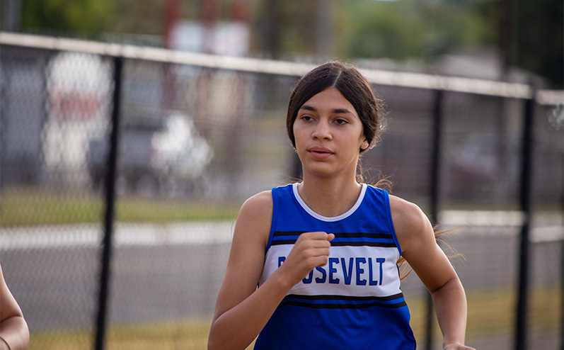 Fields & Futures Simon Greiner Track & Field Program Coach's Interview with John Zehr blog post story image of a female Roosevelt Middle School cross country athlete running in the All-City Athletic Conference cross country meet